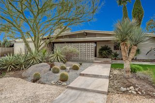 Devo Co-Founder Gerald Casale Lists His Palm Desert Midcentury For $1.2M - Photo 1 of 14 - The front garden features native landscaping.