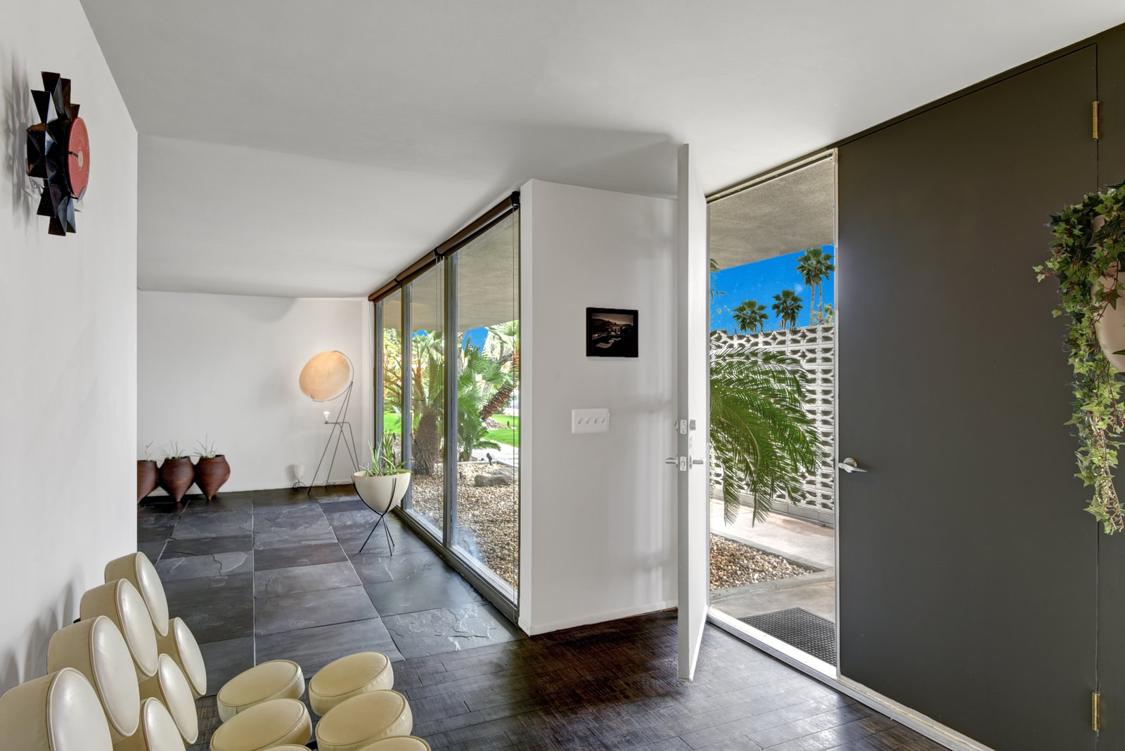 The entry hall has natural lighting thanks to floor-to-ceiling windows, and privacy thanks to an exterior privacy wall.