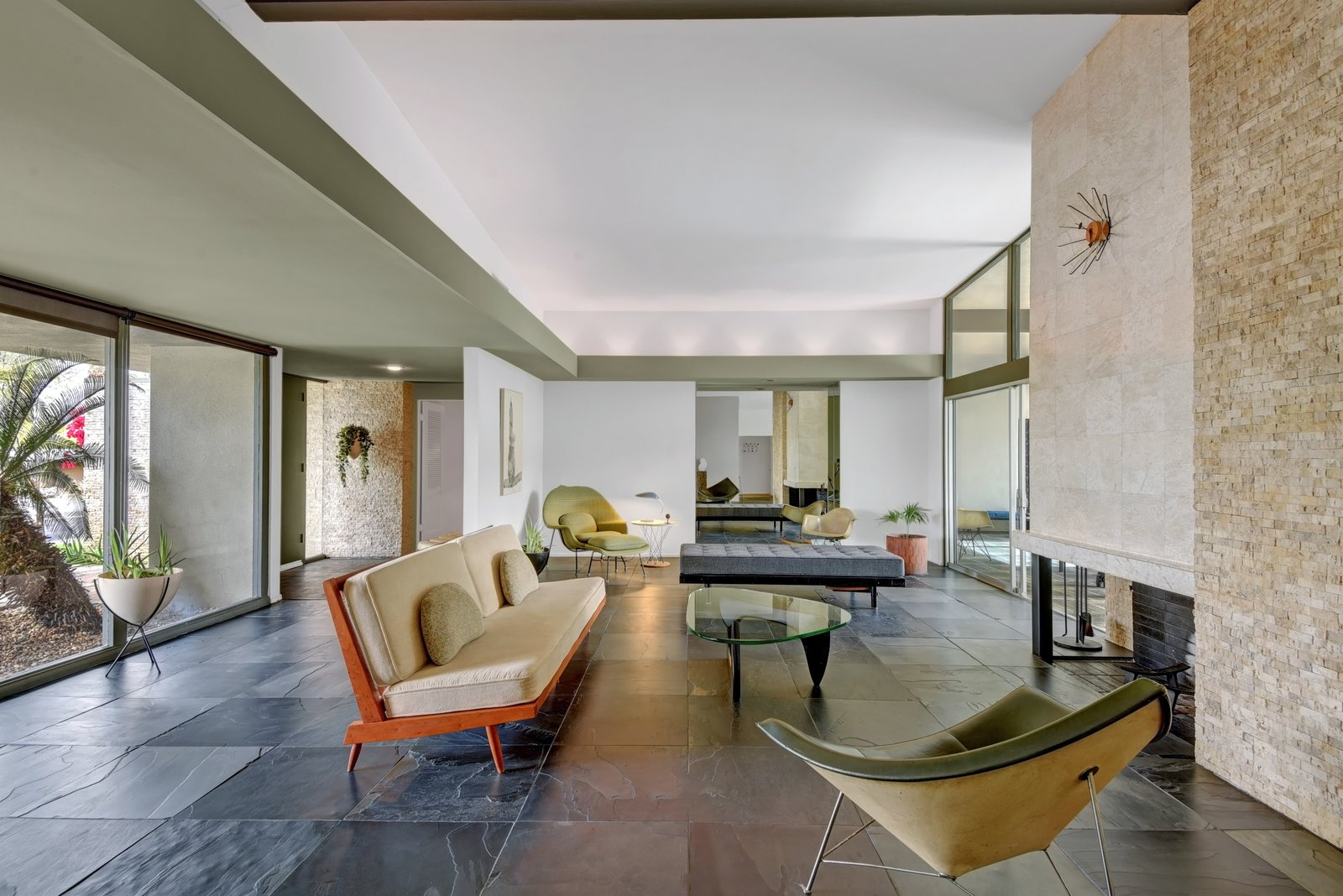 The interiors fully embrace the midcentury aesthetic, with high-beamed ceilings, slate floors, custom wood flooring, and a split rock fireplace.