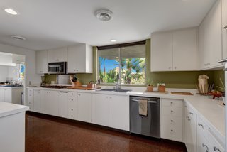 Devo Co-Founder Gerald Casale Lists His Palm Desert Midcentury For $1.2M - Photo 9 of 14 - The kitchen and prep kitchen feature stainless-steel appliances, commercial fixtures, and cork floors.