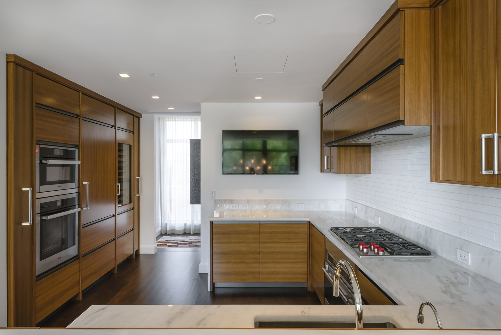 The customized open kitchen features top-of-the-line appliances.