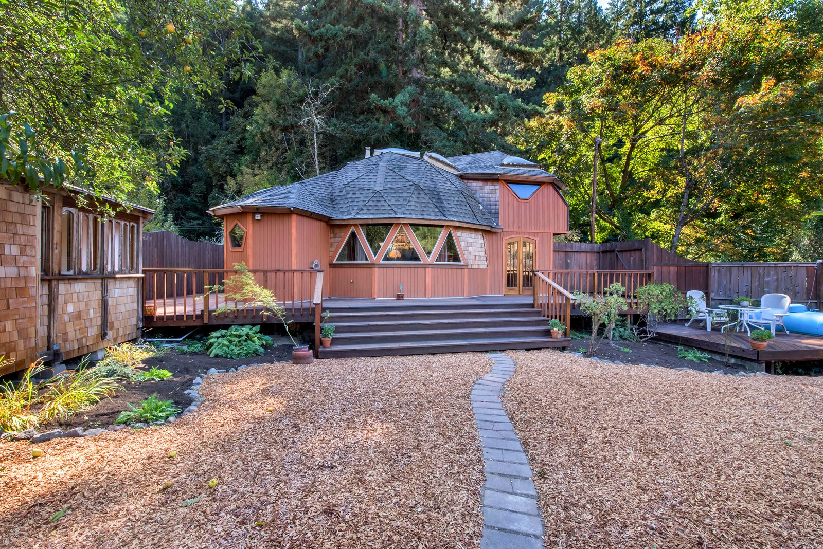 The property features not only the geodesic dome home, but also a large yard and two additional structures.