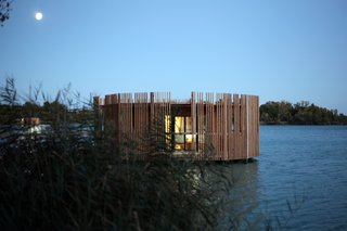 Drift Off in a Prefab Cabin at This Floating Hotel in France - Photo 11 of 13 - After sunset the effect is reversed, and a radiating internal glow emerges from between the wooden slats.