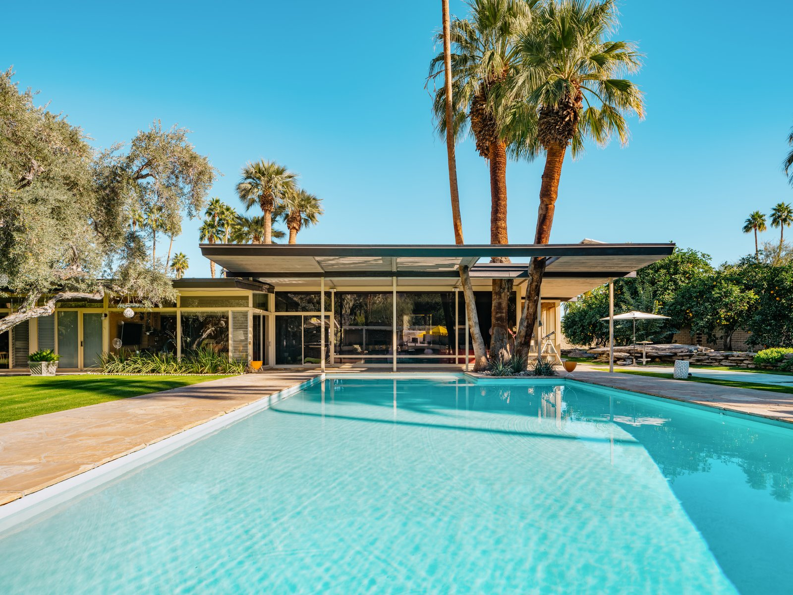 The large L-shaped estate looks out on a large pool and a luxurious outdoor entertaining area.