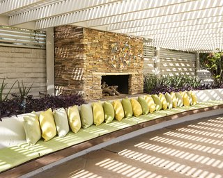 A Luminous Palm Springs Midcentury Asks $3.35M - Photo 13 of 16 - The stacked stone fireplace is perfect for entertaining on cool desert nights.