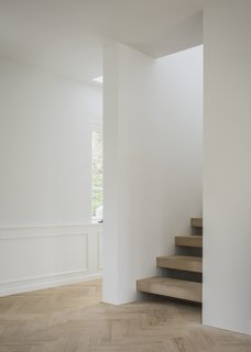 The Historic Villa Once Home to Poul Henningsen Receives a Modern Renovation - Photo 7 of 12 - A central staircase creates a dynamic, semi-open space. The floating steps in solid oak creates a flow that connects the house vertically in a harmonious and contemporary manner.