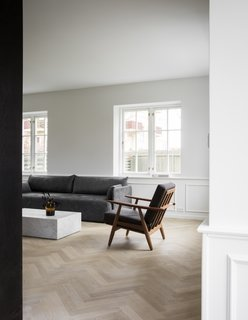 The Historic Villa Once Home to Poul Henningsen Receives a Modern Renovation - Photo 5 of 12 - Dark midcentury teak furniture and classic marble are set against a white backdrop.