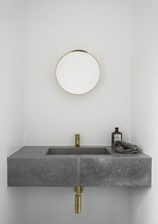 The Historic Villa Once Home to Poul Henningsen Receives a Modern Renovation - Photo 10 of 12 - Both the kitchen and bathroom of the redesigned dwelling feature slim brass faucets.
