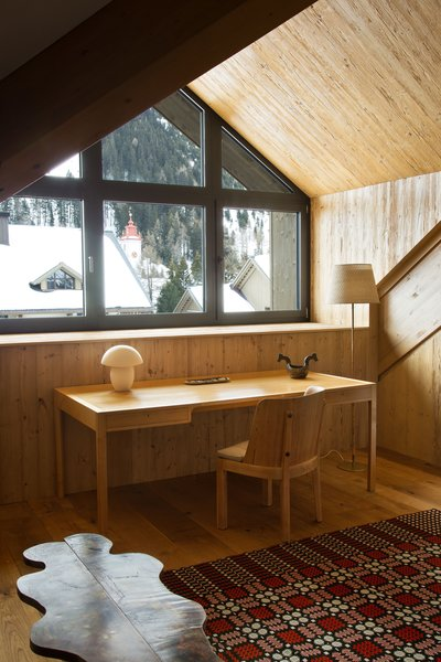A minimalist desk looks out on the alpine scenery in the master bedroom.