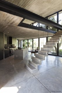A Commanding Mexican Home of Stone and Concrete Is For Sale - Photo 3 of 10 - The main living area features a full-glass frontage facing the mountains and a cut stone stairway leading to the mezzanine level.