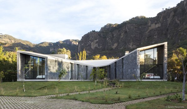 The house is a succession of three pavilions unified by a unique roof, with two covered patios.