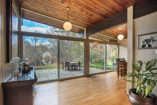 Own an Iconic Midcentury in New Canaan For $1.55M - Photo 6 of 12 - Floor-to-ceiling walls of glass allow for expansive views of the property and pond.