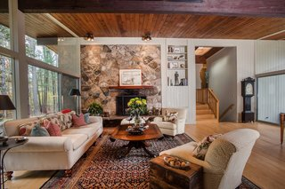 Own an Iconic Midcentury in New Canaan For $1.55M - Photo 5 of 12 - Another beautiful feature of the home is the stone fireplace.