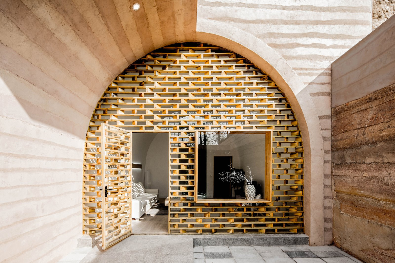 The main entrance of the main cave was transformed into a wooden grid façade and glass curtain wall, allowing ample natural light to enter the space. Tagged: Doors, Exterior, Swing, and Wood.  Best Doors Photos from An Old Cave Dwelling in Central China Is Transformed Into a Stylish Home