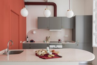 Before and After: An Ancient Barcelona Apartment Gets a Colorful, Chic Makeover - Photo 16 of 24 - Three globe pendants with brass details and burgundy cords that match the hood tube hang above the kitchen island.