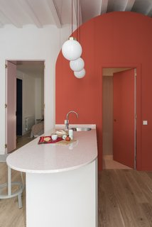 Before and After: An Ancient Barcelona Apartment Gets a Colorful, Chic Makeover - Photo 19 of 24 - The rounded island houses a sink and dishwasher, and also doubles as an informal eating area.