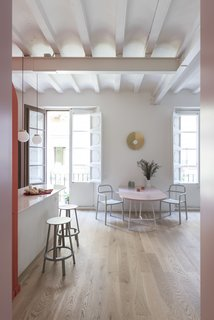 """Before and After: An Ancient Barcelona Apartment Gets a Colorful, Chic Makeover - Photo 13 of 24 - Between the two big windows, the golden """"Fold Lamp"""" presides over the dining area, which consists of a wide pink lacquered table. The Ypperlig chairs pictured above are by HAY for IKEA."""