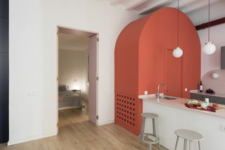 Before and After: An Ancient Barcelona Apartment Gets a Colorful, Chic Makeover - Photo 18 of 24 - An arc-shaped, coral-colored volume that hides a powder room has become a main feature of the design.