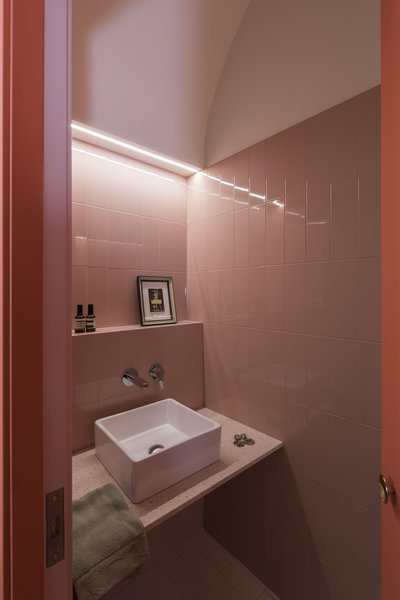 The guest bathroom sits hidden in a coral-colored arch volume off the kitchen.