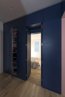 Before and After: An Ancient Barcelona Apartment Gets a Colorful, Chic Makeover - Photo 6 of 24 - The lacquered panels of the bespoke storage unit conceal direct access to the bedroom from the main entrance through a double door.