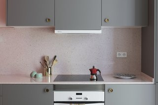 Before and After: An Ancient Barcelona Apartment Gets a Colorful, Chic Makeover - Photo 17 of 24 - The kitchen cabinets are finished in a warm gray, and are fitted with vintage, brass concave handles. The countertops are a pink terrazzo-like quartz.