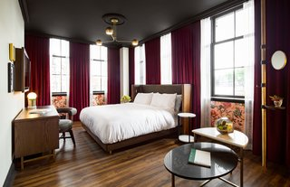 A Former Strip Club Transforms Into a Snazzy Boutique Hotel - Photo 6 of 11 - The dark velvet floor-to-ceiling curtains paired against the bronze lighting and wooden floors define the vintage vibe in the guest rooms.