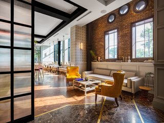 A Former Strip Club Transforms Into a Snazzy Boutique Hotel - Photo 2 of 11 - The ground-floor cafe features large street-facing windows and plenty of natural light.