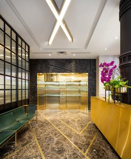 A Former Strip Club Transforms Into a Snazzy Boutique Hotel - Photo 4 of 11 - The lobby now houses a vibrant mix of granite and gold.