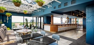 A Former Strip Club Transforms Into a Snazzy Boutique Hotel - Photo 9 of 11 - A glass volume was inserted on the roof to host the lounge and bar. Blue walls and brass pendant lighting in the area are juxtaposed against the bright and airy dining space.
