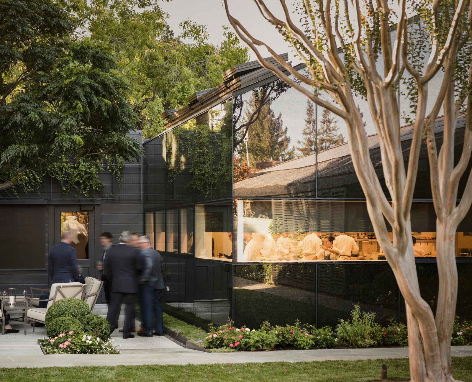 The pitched, low-slung roofs of the kitchen and annex allude to their utilitarian function. Tagged: Exterior, Wood Siding Material, Gable RoofLine, and Glass Siding Material.  Best Photos from A Look Inside The French Laundry's Stunning $10M Renovation