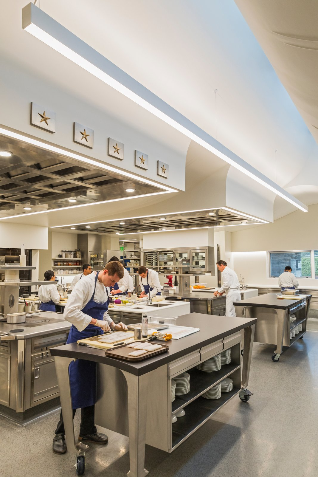 The 2,000-square-foot kitchen provides a comfortable, light-filled working space for the chefs and is configured as a single, continuous space. Tagged: Kitchen, Metal Cabinet, Cooktops, Recessed Lighting, and Terrazzo Floor.  Best Photos from A Look Inside The French Laundry's Stunning $10M Renovation