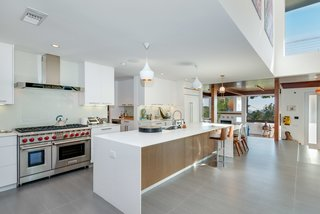 A Renovated Harry Gesner–Designed Midcentury in L.A. Wants $9.4M - Photo 5 of 15 - The updated open kitchen features state-of-the-art appliances from Sub Zero and Wolf, and Caesarstone countertops.