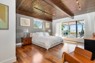 A Renovated Harry Gesner–Designed Midcentury in L.A. Wants $9.4M - Photo 8 of 15 - The second bedroom also has outdoor access with Fleetwood sliding doors.