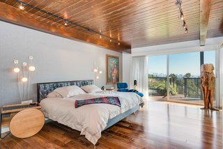 A Renovated Harry Gesner–Designed Midcentury in L.A. Wants $9.4M - Photo 7 of 15 - The master bedroom on the upper level features hardwood floors and redwood ceilings, and opens to a terrace.