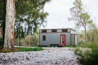 """12 Tiny House Companies That Can Make Your Micro-Living Dreams Come True - Photo 4 of 12 - Based in Chattanooga, Tennessee, Wind River Tiny Homes designs and crafts tiny homes. They can build from pre-existing plans or design a completely customized house. They also promote """"right-sized living"""" through hands-on workshops that teach tiny house building practices. This model, The Chimera, blends modern, rustic, and industrial styles, and features an off-grid solar system, custom shower, custom kitchen, and premium appliances. The Chimera goes for around $88,000."""