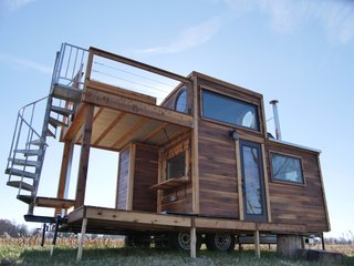 """12 Tiny House Companies That Can Make Your Micro-Living Dreams Come True - Photo 6 of 12 - The """"Honey on the Rock"""" from tiny home maker Carpenter Owl (who specializes in custom projects) is their """"most ambitious build to date."""" Originally created as a vacation home, this dwelling has fun features such as a spiral staircase, two decks, and even enough space for a king size bed. This home starts at $85,000."""