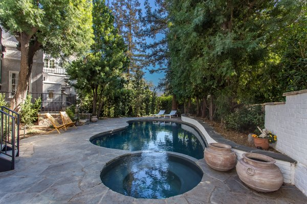 The pool and hot tub complete the private and shaded backyard.