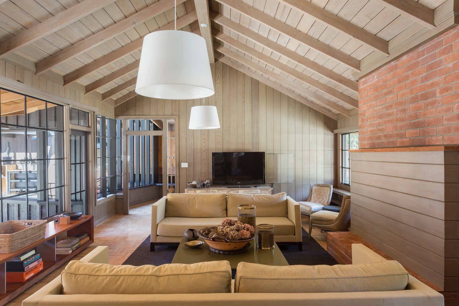 With original steel-framed windows, beamed ceilings, warm wood-paneled walls, and a gracious floor plan it makes for a wonderful entertaining space.