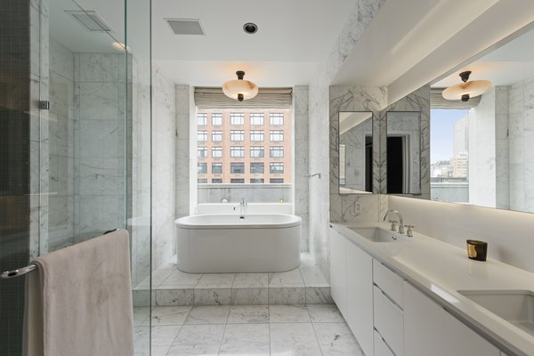 The master bath features Statuary marble, radiant heat floors, a Kaldewei Vaio Duo oval freestanding tub, a frameless glass-enclosed shower, Lefroy Brooks fixtures and a Valcucine vanity.
