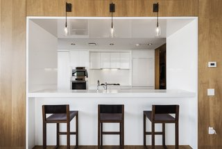 Own Justin Timberlake's Posh Soho Penthouse For $8M - Photo 2 of 8 - The Gwathmey Siegel–designed kitchen boasts Valcucine cabinetry of striated elm and smoked glass, Jet Mist granite, a Sub-Zero refrigerator, a Miele oven and dishwasher, a Gaggenau cooktop and fully vented hood, wine storage, and a cut-out breakfast bar that opens to the living room.