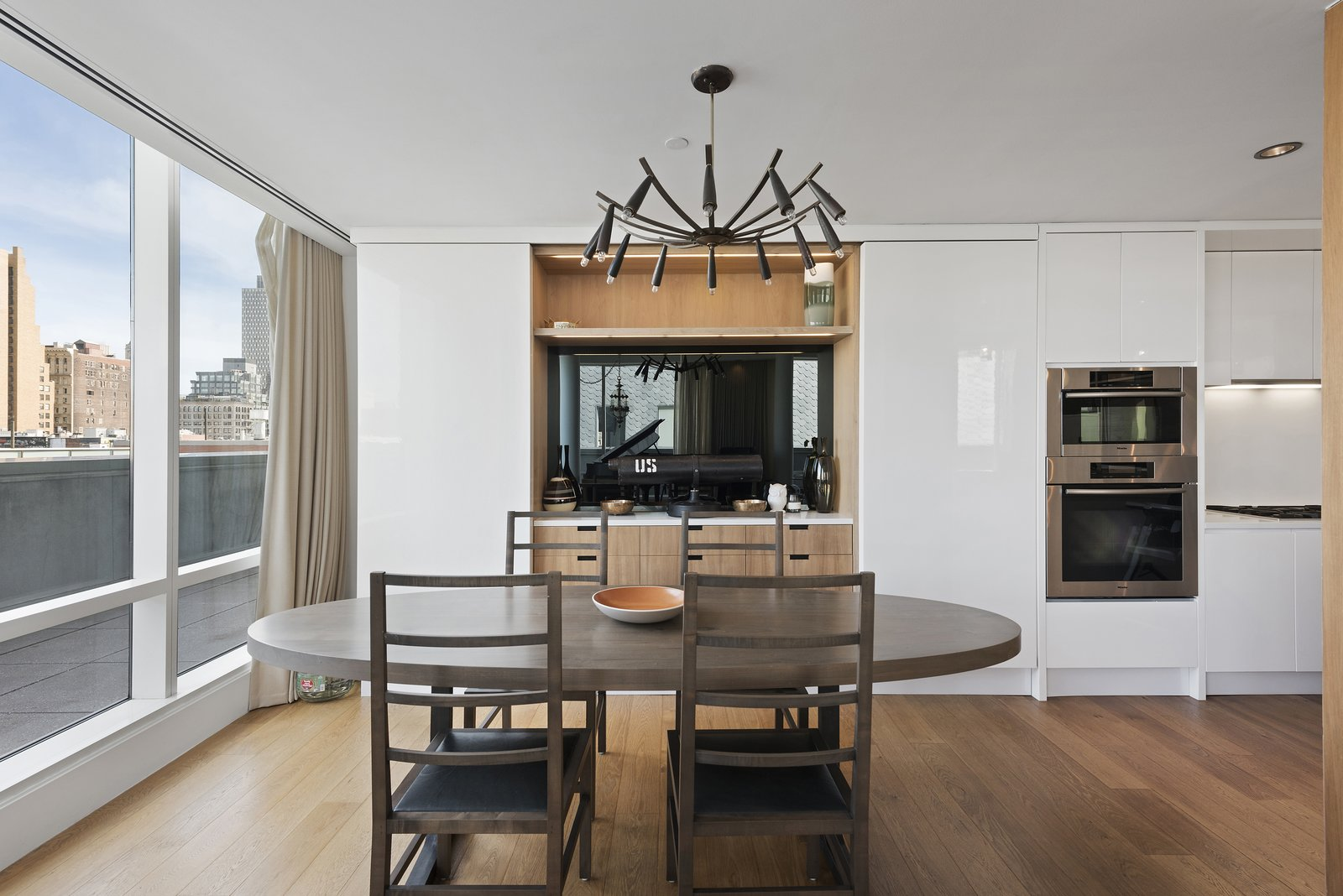 The living/dining area wraps around a central open kitchen and looks out on the wraparound terrace. The home features many state-of-the features such as a Creston electronic shade system throughout.