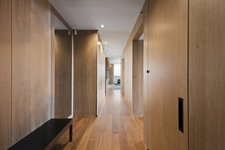 Own Justin Timberlake's Posh Soho Penthouse For $8M - Photo 4 of 8 - Wood-paneled walls concealing storage line the corridor and play off the unit's oak wood flooring.