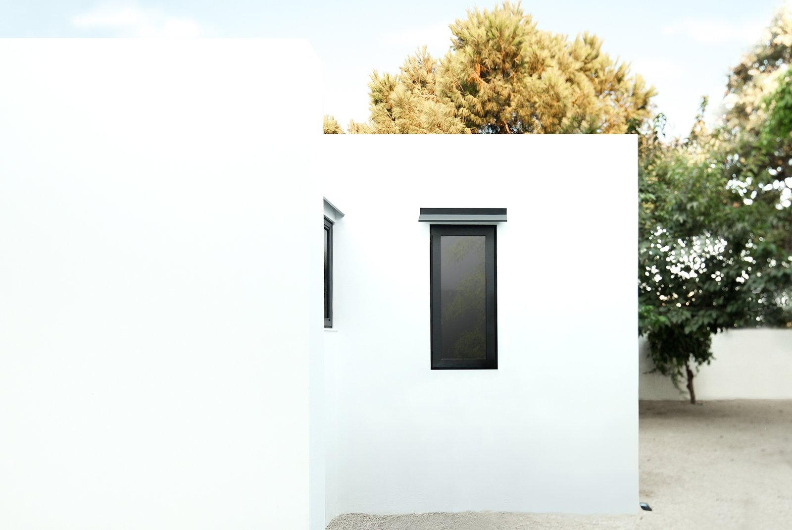 The home's whitewashed exterior references Greek island architecture.