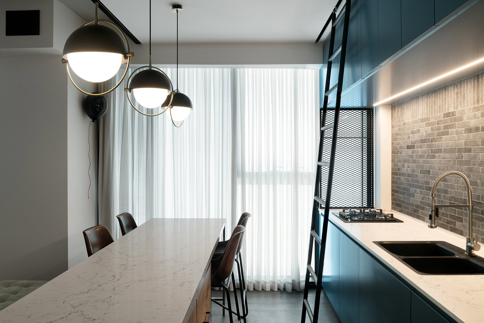 Surrounded by floor-to-ceiling windows on all sides, the material palette for the unit includes contemporary industrial touches such as iron, glass, and wood.