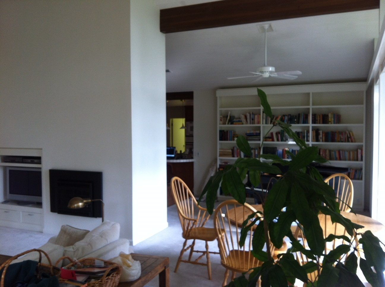 A view of the dining room area from the living room before the renovations. Drywall covers the fireplace and a built-in bookcase is at the rear.