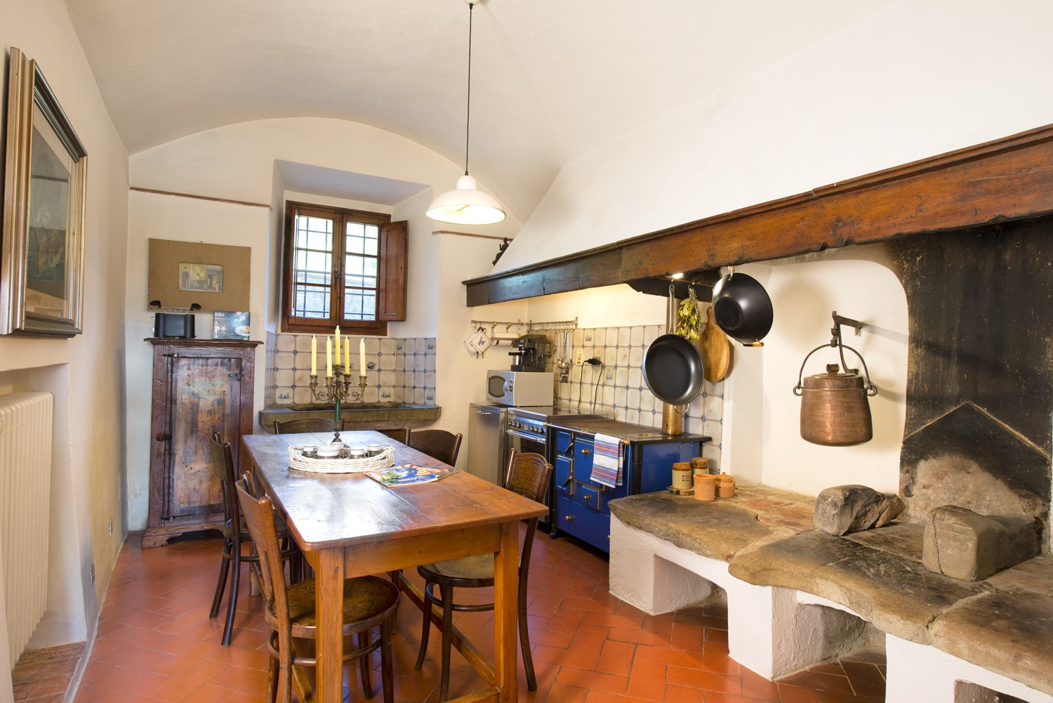 The kitchen features an original stone hearth and basin.