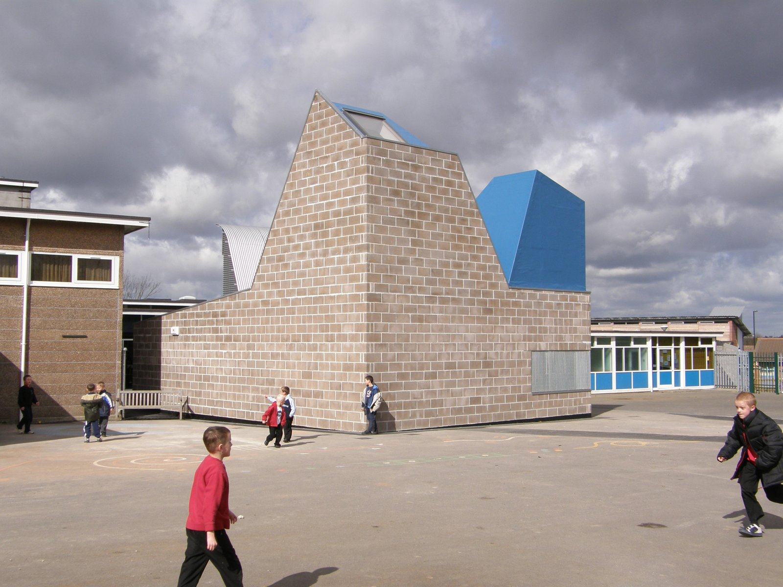 The building uses raw concrete block externally, and internally is finished with bare plywood, OSB and a varnished concrete screed.