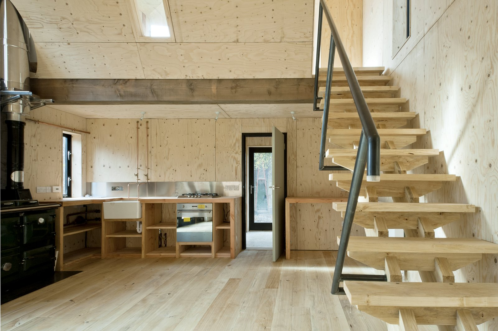 The construction process was super-efficient, even the joinery was manufactured on site. The kitchen (which uses exposed copper piping for taps) has chunky timber worktops, and the stairs use an innovative dry jointed system that gains strength as the timber dries. The handrail is made of mild steel bent piping, which was also welded on site.