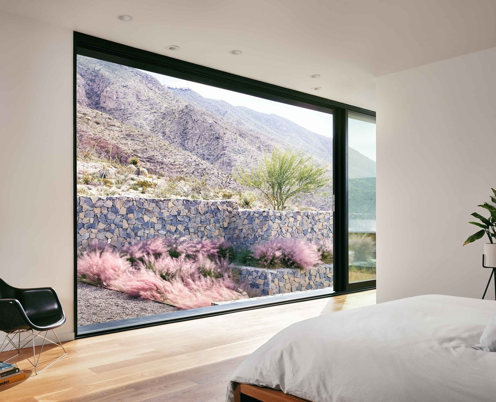 A multi-slide door in the master suite opens up to the natural mountain preserve. Tagged: Bedroom and Light Hardwood Floor. West Texas Vistas by Western Window Systems