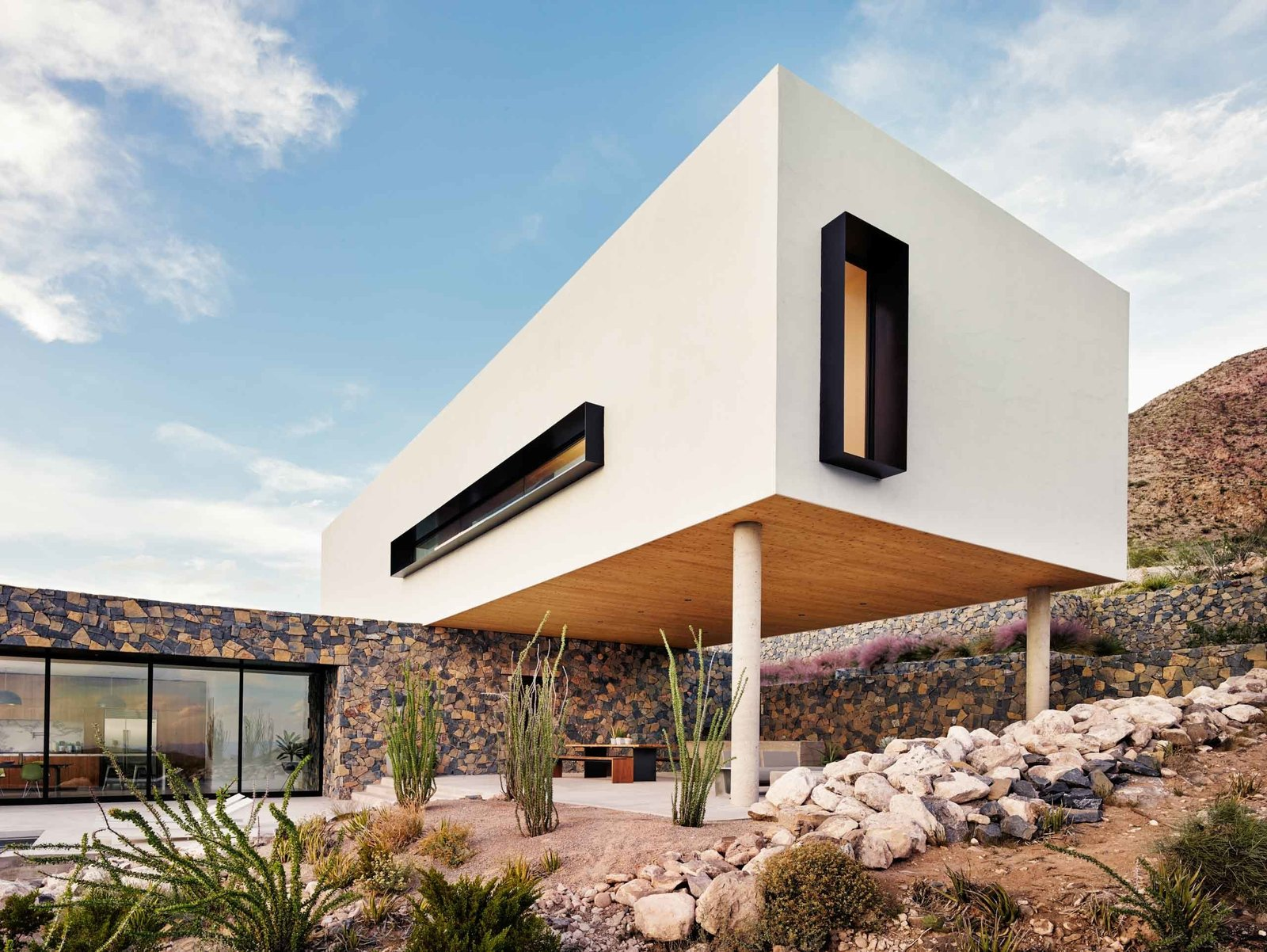 The white stucco volume stands out amid the rocky terrain of the Franklin Mountains near El Paso.  West Texas Vistas by Western Window Systems